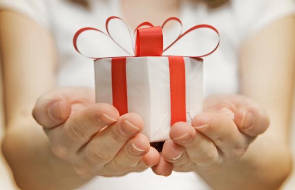 main portant un petit cadeau blanc décoré d'un ruban rouge