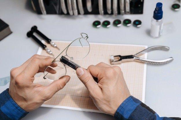 photo en gros plan des mains d'un opticien qui répare des lunettes