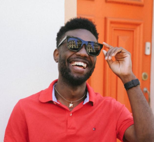 Jeune homme heureux qui porte des solaires